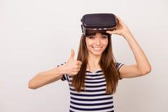 Opgewekt jong glimlachend meisje die duim na het gebruiken van beschermende brillen tonen stock foto's