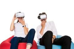 Opgewekt jong paar die virtuele werkelijkheid gezet die op beanbags ervaren op witte achtergrond wordt geïsoleerd Stock Afbeeldingen