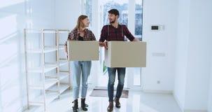 Opgewekt jong paar die zich aan een nieuw ruim huis in een zonnige dag bewegen glimlachen zij het houden van grote dozen en genie stock video