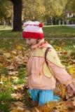 Opgewekt meisje in de herfstbladeren Stock Foto
