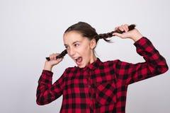 Opgewekt meisje die haar haar trekken, dat twee staarten heeft en gekleed in een rood plaidoverhemd is royalty-vrije stock afbeeldingen