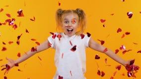 Opgewekt meisje die hart-vormige confettien werpen in lucht, kinderenpartij, langzaam-mo stock footage