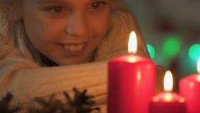 Opgewekt meisje die het branden van kaarsen bekijken, die wens op Kerstmis, close-up maken stock video