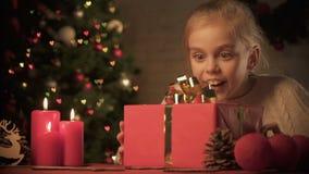 Opgewekt meisje die Kerstmis huidig op lijst met prachtige decoratie bekijken stock footage