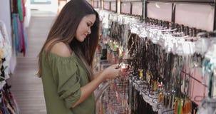 Opgewekt meisje die vertoning in winkel onderzoeken stock video