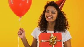 Opgewekt meisje met giften die voor camera, kortingen en bevorderingen voor verjaardag stellen stock footage