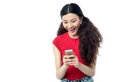 Opgewekt mooi meisje die een tekstbericht verzenden Royalty-vrije Stock Foto's