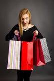 Opgewekt mooi meisje die haar het winkelen zakken onderzoeken Royalty-vrije Stock Foto's