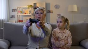 Opgewekt oma het spelen videospelletje die droevige de bankverslaving negeren van de kleinkindzitting stock footage
