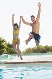 Opgewekt paar dat in zwembad op vakantie springt Royalty-vrije Stock Foto