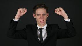 Opgewekt zakenman het vieren succes, donkere zwarte achtergrond stock footage