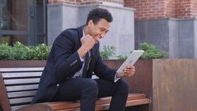 Opgewekte Afrikaanse Zakenman Celebrating Success op tabletzitting op Bank royalty-vrije stock foto