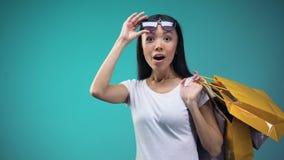 Opgewekte Aziatische dame die showcases met bevorderingen en kortingen, het winkelen bekijken stock footage