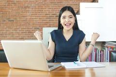 Opgewekte Aziatische vrouw die haar wapens opheffen terwijl het werken aan haar laptop royalty-vrije stock foto