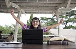 Opgewekte Aziatische vrouw met laptop en boeken royalty-vrije stock afbeeldingen
