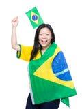 Opgewekte Aziatische vrouwenholding en het draperen met de vlag van Brazilië Stock Foto