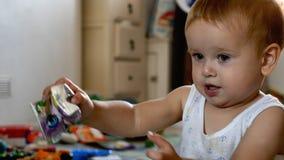 Opgewekte babyjongen die plastic pak zak gezichtsweefsels thuis geven aan hond stock afbeeldingen
