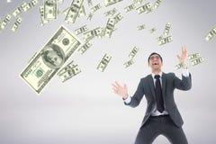 Opgewekte bedrijfsmens die geldregen tegen witte achtergrond bekijken Royalty-vrije Stock Foto