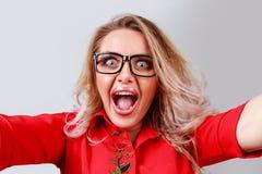 Opgewekte blondevrouw die selfie in studio nemen stock foto's