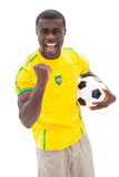Opgewekte Braziliaanse voetbalventilator die holdingsbal toejuichen Stock Foto's