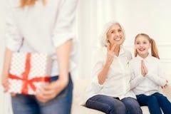 Opgewekte dochter en hogere dame die op heden van mamma wachten stock fotografie