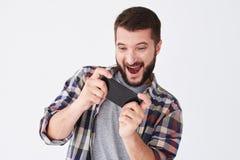 Opgewekte gebaarde mens in het gecontroleerde overhemd spelen op smartphone Royalty-vrije Stock Fotografie