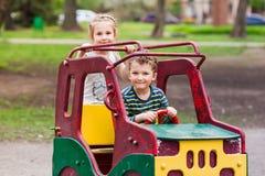 Opgewekte gelukkige jonge geitjes die een stuk speelgoed auto drijven Stock Foto's