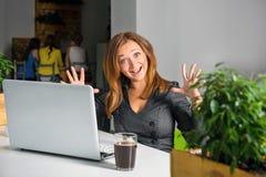 Opgewekte gelukkige onderneemster die met opgeheven wapens bij de lijst met laptop zitten die haar succes vieren Grappig beeld va Stock Foto