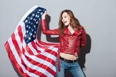 Opgewekte gelukkige vrouw in de rode vlag van de de holdingsv.s. van het leerjasje Stock Afbeelding