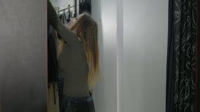 Opgewekte glimlachende bedrijfsvrouw die proberend jasjes in de montageruimte en controlerend haar verschijning in de spiegel win stock video