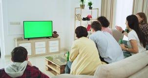 Opgewekte groep multi etnische vrienden die op een voetbalwedstrijd in TV met het groen scherm letten zij gelukkige steun en stock video