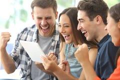 Opgewekte groep vrienden die op TV van tablet letten stock afbeeldingen