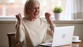 Opgewekte hogere vrouw die winnaar voelen die goed online nieuws lezen
