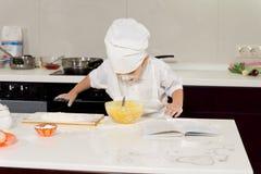 Opgewekte jonge chef-kok die over het mengen van kom leunen Royalty-vrije Stock Afbeelding