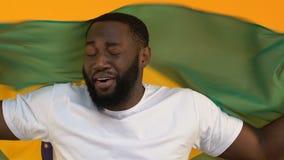 Opgewekte jonge mannelijke holdingsvlag van Brazilië op gele achtergrond, ondersteunend team stock footage