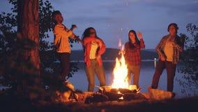 Opgewekte jonge mannen en vrouwenhipsters dansen rond helder kampvuur die openluchtpartij in bos hebben die pret hebben stock video