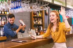 Opgewekte jonge meisjeszitting bij de barteller en het golven aan haar vrienden stock fotografie