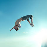 Opgewekte jonge mens die in lucht springt Royalty-vrije Stock Afbeeldingen
