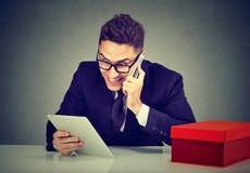 Opgewekte jonge mens die online orde over de telefoon plaatsen die tabletcomputer met behulp van stock foto's