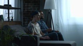 Opgewekte jonge mensen die op sporten op TV thuis letten stock videobeelden