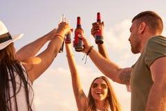 Opgewekte jonge vrienden die met flessen roosteren royalty-vrije stock foto's