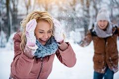 Opgewekte jonge vrouw die hoofd van sneeuwbal behandelen Stock Foto