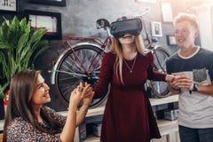 Opgewekte jonge vrouw die interactief videospelletje spelen die virtuele werkelijkheidshoofdtelefoon met vrienden dragen die haar royalty-vrije stock afbeelding