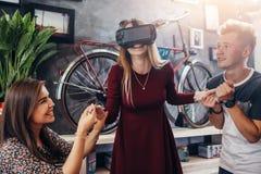 Opgewekte jonge vrouw die interactief videospelletje spelen die virtuele werkelijkheidshoofdtelefoon met vrienden dragen die haar stock foto