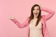 Opgewekte jonge vrouw die jasje dragen die hand op hoofd zetten, die wijsvinger richten die opzij op pastelkleur roze muur wordt  royalty-vrije stock afbeelding