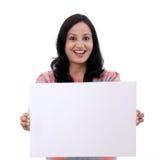 Opgewekte jonge vrouw die lege witte raad houdt Stock Foto's