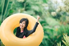 Opgewekte jonge vrouw met opblaasbare buis in een pool royalty-vrije stock foto's