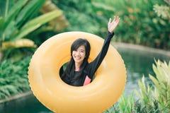 Opgewekte jonge vrouw met opblaasbare buis in een pool stock foto