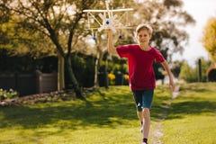 Opgewekte jongen die met een stuk speelgoed vliegtuig lopen stock fotografie