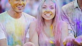 Opgewekte jongeren die gekleurd poeder in lucht werpen, die met geluk glanzen stock footage